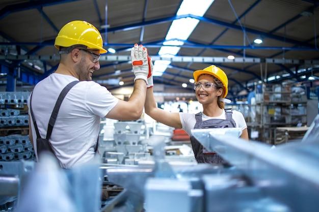 Los trabajadores de la fábrica se saludan por el éxito del trabajo en equipo