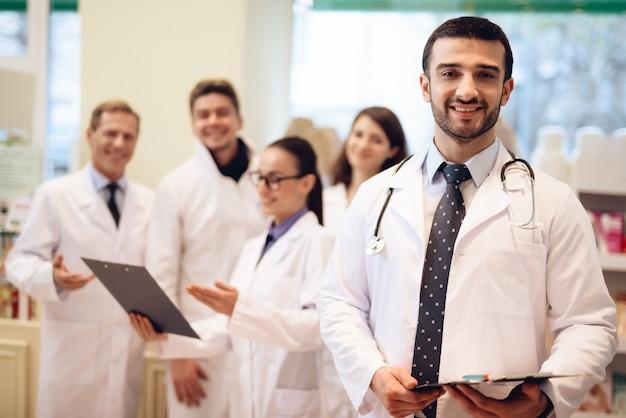 Los trabajadores de farmacia en batas blancas posando en la cámara.