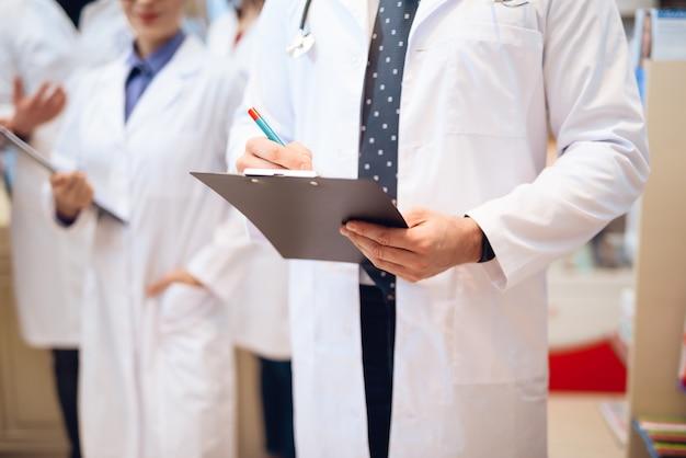 Los trabajadores de la farmacia en batas blancas posando en la cámara.