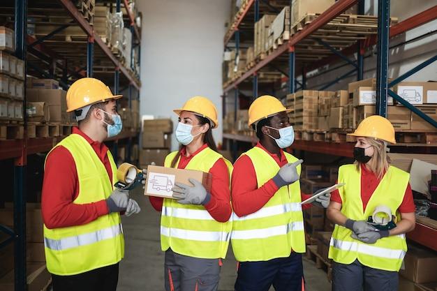Trabajadores felices hablando dentro del almacén mientras usan máscaras de seguridad durante el brote de coronavirus - focus center faces