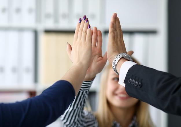 Trabajadores felices en la oficina celebrando nuevos logros corporativos