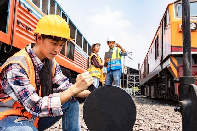 Trabajadores industriales asiáticos tiran del interruptor del ferrocarril para que el tren se desvíe de la ruta original