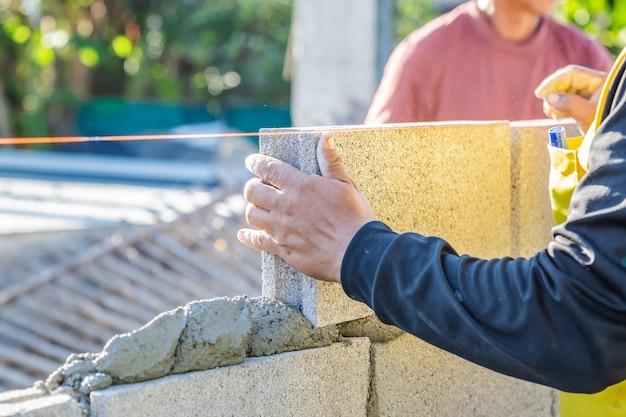 Los trabajadores de mampostería están construyendo muros con bloques de cemento y mortero mediante la construcción en capas.