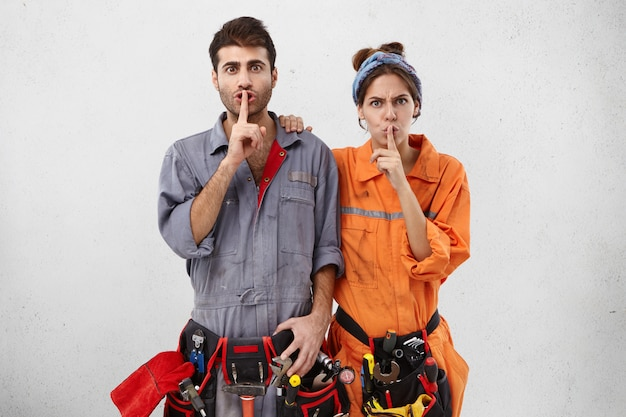 Trabajadores de mantenimiento en cinturones de herramientas y unform especiales