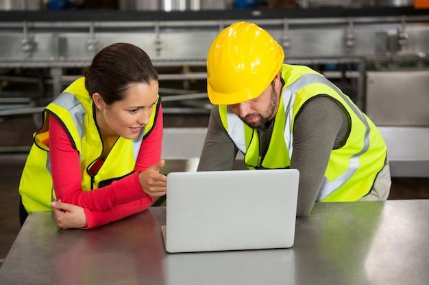 Trabajadores manuales con laptop en la fábrica.