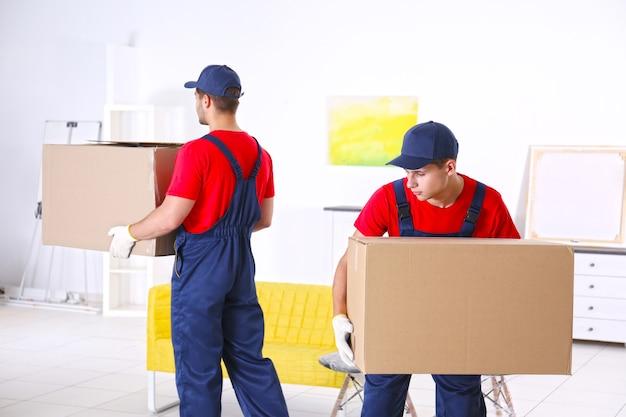 Trabajadores masculinos con cajas y muebles en casa nueva