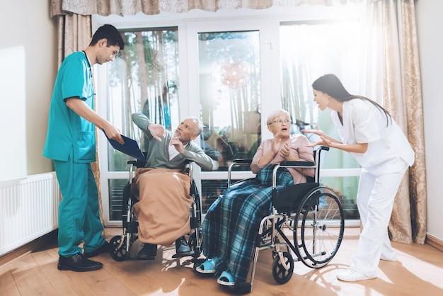 Trabajadores médicos discuten con una pareja de ancianos en un hogar de ancianos