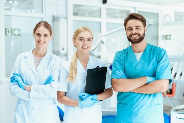 Trabajadores médicos con equipo de dentista de pie y sonriente.
