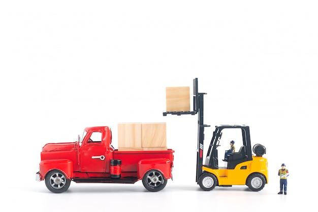 Trabajadores en miniatura cargando carga en la recogida
