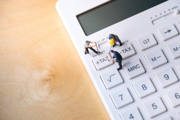 Trabajadores en miniatura cavando botón de impuestos en la calculadora