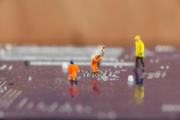 Trabajadores miniatura que trabajan en el chip de la placa base