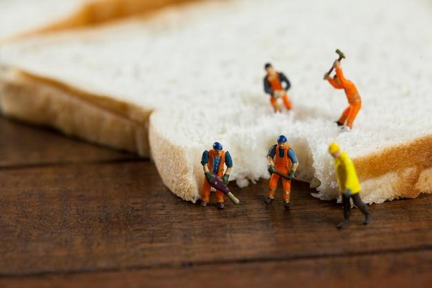 Trabajadores miniatura que trabajan en rodajas de pan