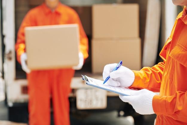 Trabajadores de mudanzas domésticas marcando casillas