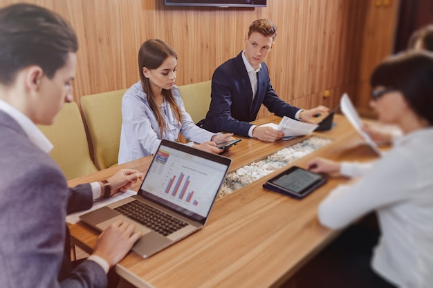 Los trabajadores de oficina celebran una reunión en un escritorio para computadoras portátiles, tabletas y papeles, un televisor grande en una pared de madera