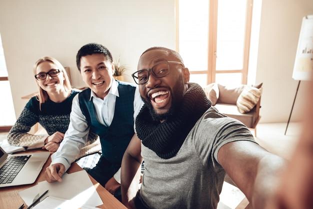 Los trabajadores de oficina positivos selfie estudiantes se divierten.