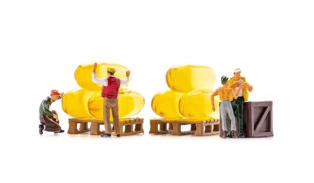 Los trabajadores de personas en miniatura transportan cápsulas de suplemento de aceite de pescado aisladas sobre fondo blanco, la atención médica y el concepto de negocio médico.