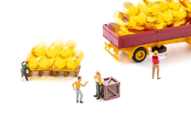 Los trabajadores de personas en miniatura transportan cápsulas de suplemento de aceite de pescado en camión aislado sobre fondo blanco, concepto de negocio médico y de atención médica.