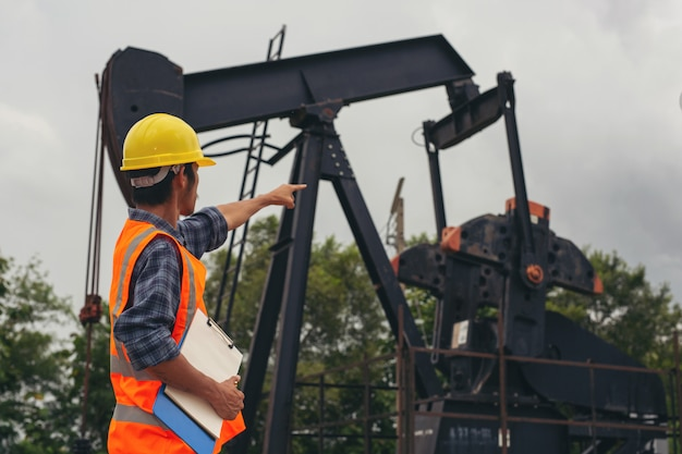 Trabajadores de pie y comprobando al lado de bombas de aceite.