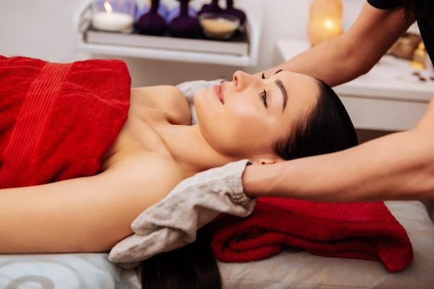 Trabajadores profesionales. mujer tranquila y paciente con cabello largo oscuro que se siente muy bien durante el procedimiento para una textura de piel más suave
