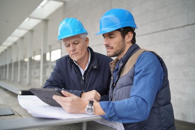 Trabajadores que consultan sobre plano con la tableta en vista del edificio moderno