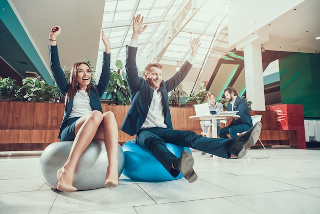 Trabajadores que ejercitan estirando los brazos en la oficina.