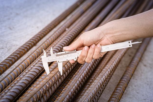 Trabajadores que utilizan una medida verniercaliper de barras de refuerzo. construcción, acero, ingeniería, refuerzo.