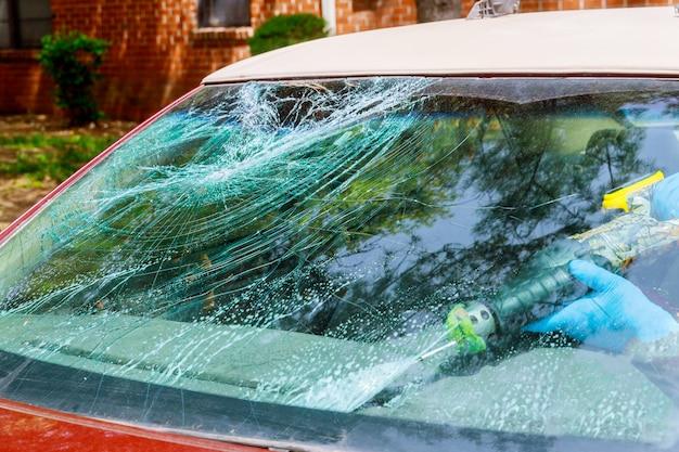 Trabajadores remotion automóvil roto parabrisas o parabrisas de un automóvil en auto servicio