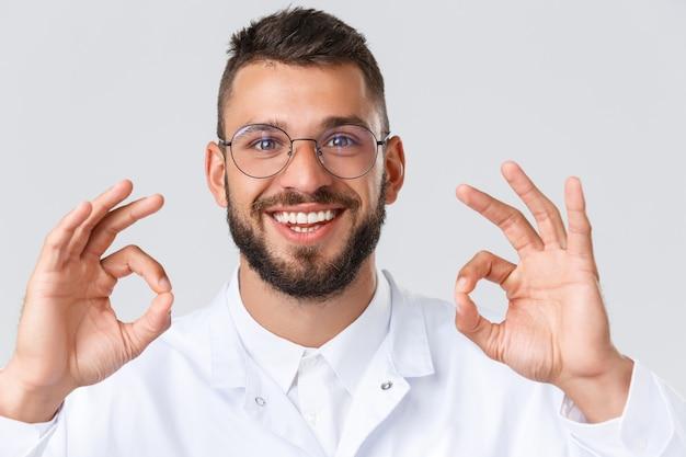 Trabajadores de la salud, coronavirus, pandemia de covid-19 y concepto de seguro. primer plano del médico entusiasta con gafas y batas blancas, muestra el signo de estar bien, aprueba la medicación, una idea increíble, sonriendo.