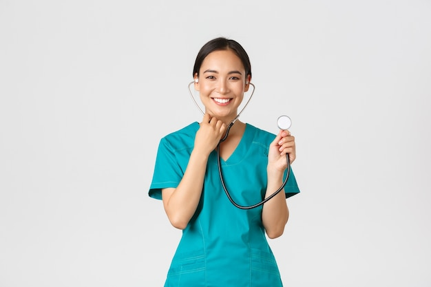 , trabajadores de la salud y prevención del concepto de virus. alegre sonriente médico de sexo femenino asiático, médico consultar al paciente, examinar a la persona con estetoscopio, pared blanca de pie.