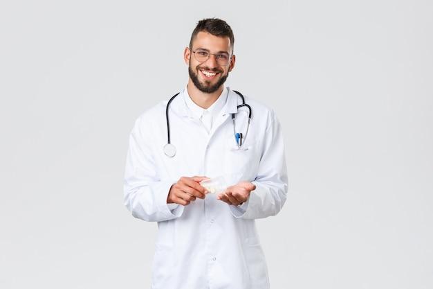 Trabajadores de la salud, seguro médico, concepto de pandemia y covid-19. hermoso médico sonriente con bata blanca y gafas, sosteniendo la medicina en la mano, consejo sobre el uso de medicamentos o antibióticos.