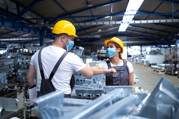 Los trabajadores se saludan con un codazo debido a la pandemia mundial del virus corona y al peligro de infección