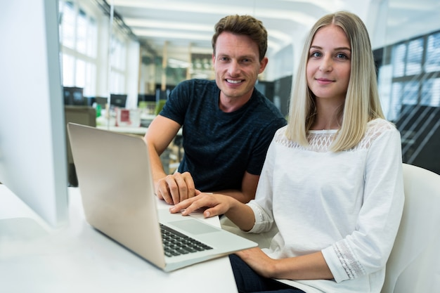 Trabajadores sonriendo delante de un portátil
