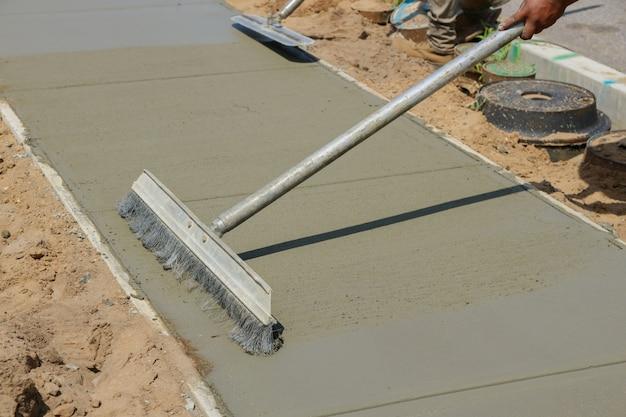 Los trabajadores terminan y alisan la superficie de concreto en la nueva acera de cemento