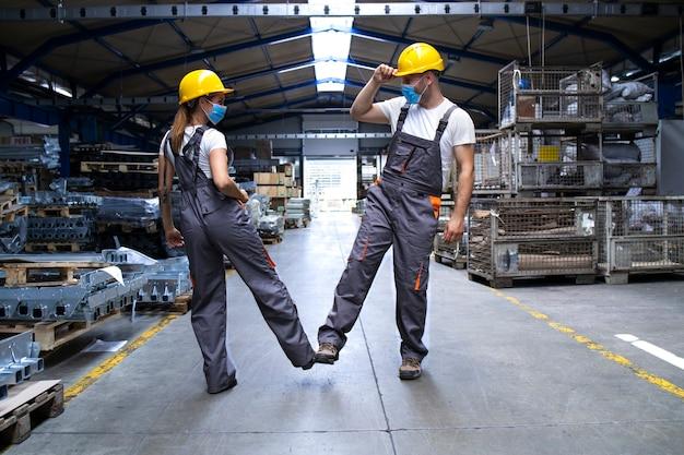 Trabajadores vestidos con uniformes y casco en la fábrica tocándose con las piernas y saludando debido al virus de la corona y la infección