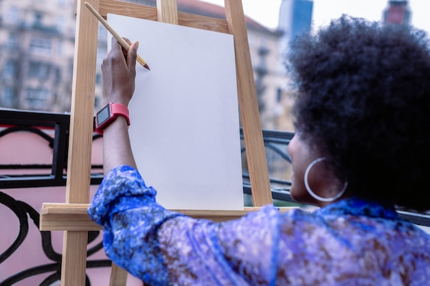 Trabajando afuera. artista talentoso afroamericano vistiendo rojo reloj inteligente trabajando fuera