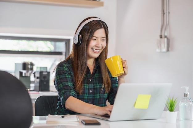 Trabajando en casa en concepto de pandemia covid-19, mujer asiática que trabaja en casa