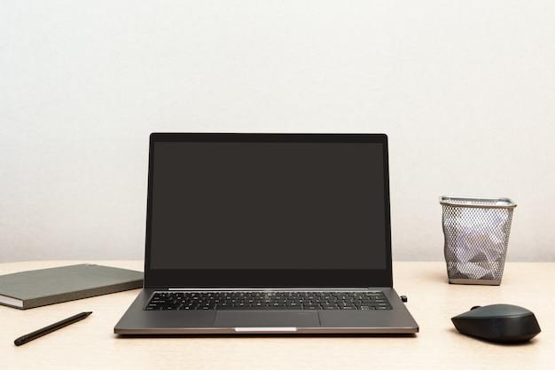 Trabajando desde casa. escritorio para capacitación en línea o trabajo remoto. cómodo lugar de trabajo para autónomos con computadora portátil abierta.