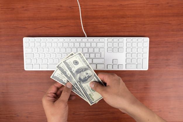 Trabajando en casa con hombres portátiles escribiendo un blog. escribiendo en un teclado. programador o pirata informático, dólares, comercio en línea
