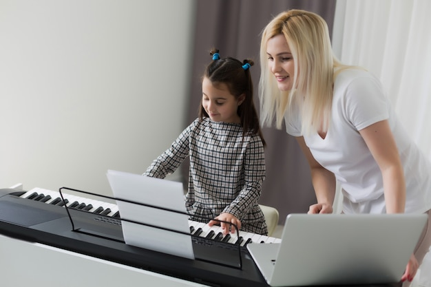 Trabajando desde casa con un niño. hija feliz abrazando a la madre. mujer joven y niño lindo que usa la computadora portátil. lugar de trabajo independiente. negocios femeninos, educación a distancia. momento familiar de estilo de vida.