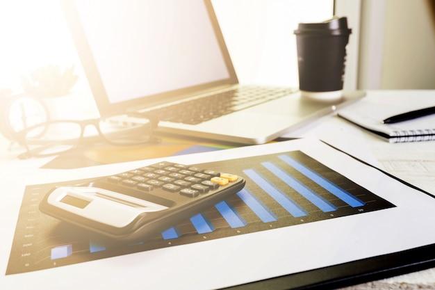 Trabajando en la computadora portátil de escritorio con calculadora para hacer negocios,