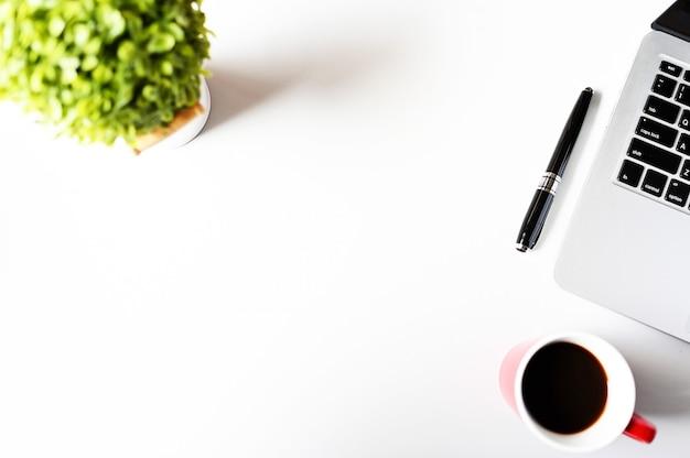 Trabajando con computadora portátil y planta y espacio de copia de café en el fondo de la mesa moderna. espacio de trabajo plano estilo minmal, concepto de negocio