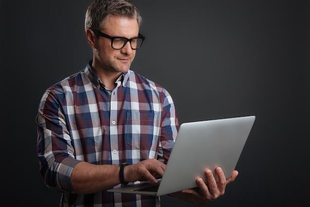 Trabajando desde cualquier lugar. chico guapo motivado enfocado escribiendo un correo electrónico mientras usa su computadora portátil y usa las gafas