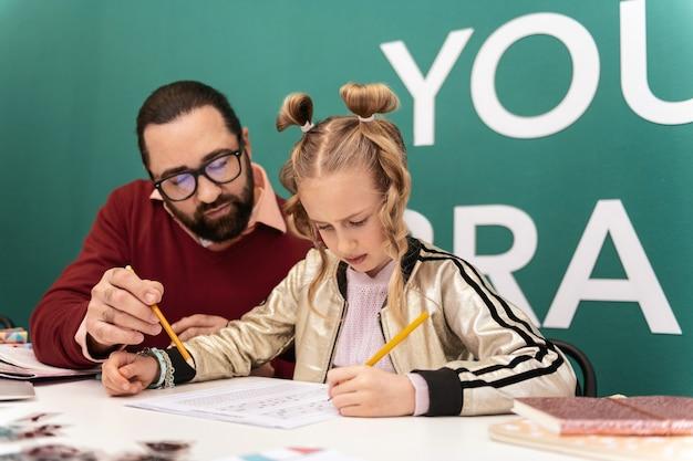 Trabajando duro. profesor adulto barbudo de pelo oscuro con gafas y su alumno mirando concentrado mientras trabaja en la lección