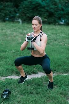 Trabajando fuera mujer atlética bastante rubia que bombea los músculos con pesas de gimnasia