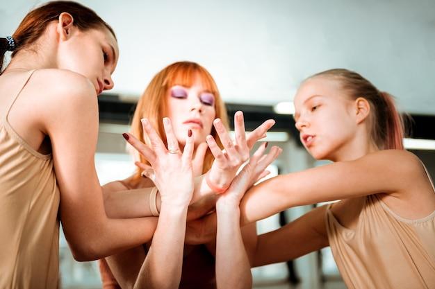 Trabajando juntos. hermosa profesora de baile con cabello rojo y sus alumnos se ven serios mientras trabaja en movimientos de manos