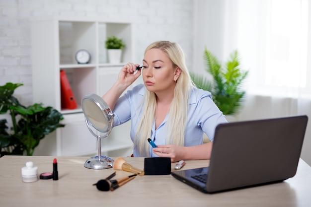 Trabajando en línea - retrato de hermosa mujer rubia de talla grande usando laptop y aplicando maquillaje en casa