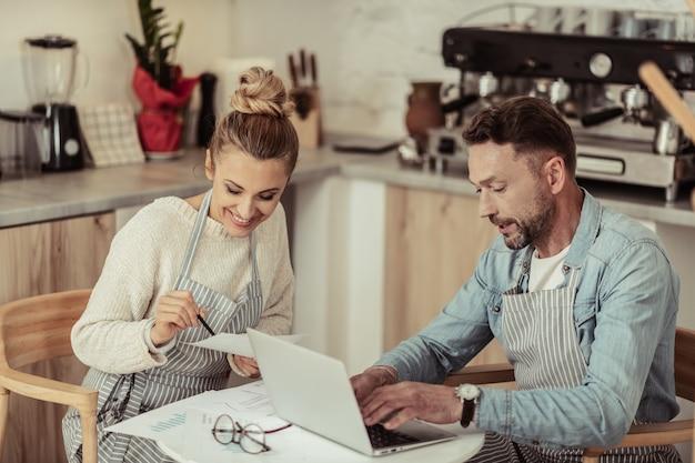 Trabajando con una sonrisa. dos sonrientes personas concentradas sentadas en la mesa de café trabajando en su proyecto común.