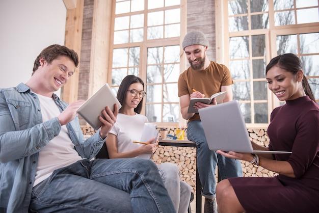 Trabajando tan duro. gente alegre, positiva y encantada sosteniendo sus dispositivos y participando en el trabajo mientras está sentado en la oficina.