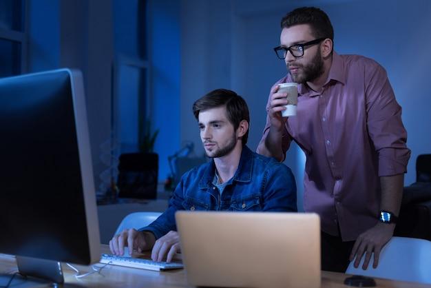 Trabajando con tecnología moderna. programador masculino atractivo agradable escribiendo en el teclado y mirando la pantalla de la computadora mientras trabaja con su colega