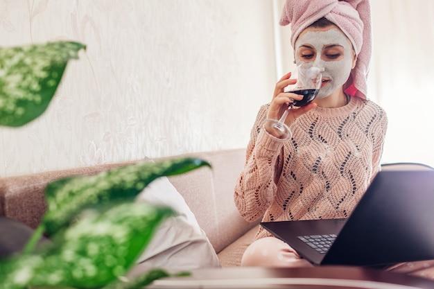 Trabajar desde casa durante la cuarentena de coronavirus. mujer con máscara facial aplicada bebiendo vino usando laptop en bloqueo
